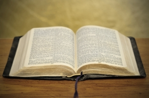 Old dusty well-used bible on timber table with golden background